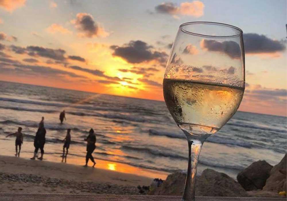 תמונת אווירה כוס יין רקע שקיעה