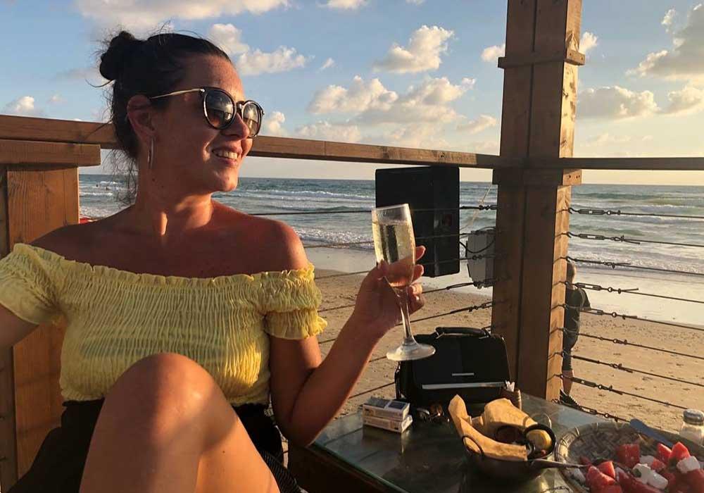 לקוחה בנירוונה חיפה עם יין על רקע ים