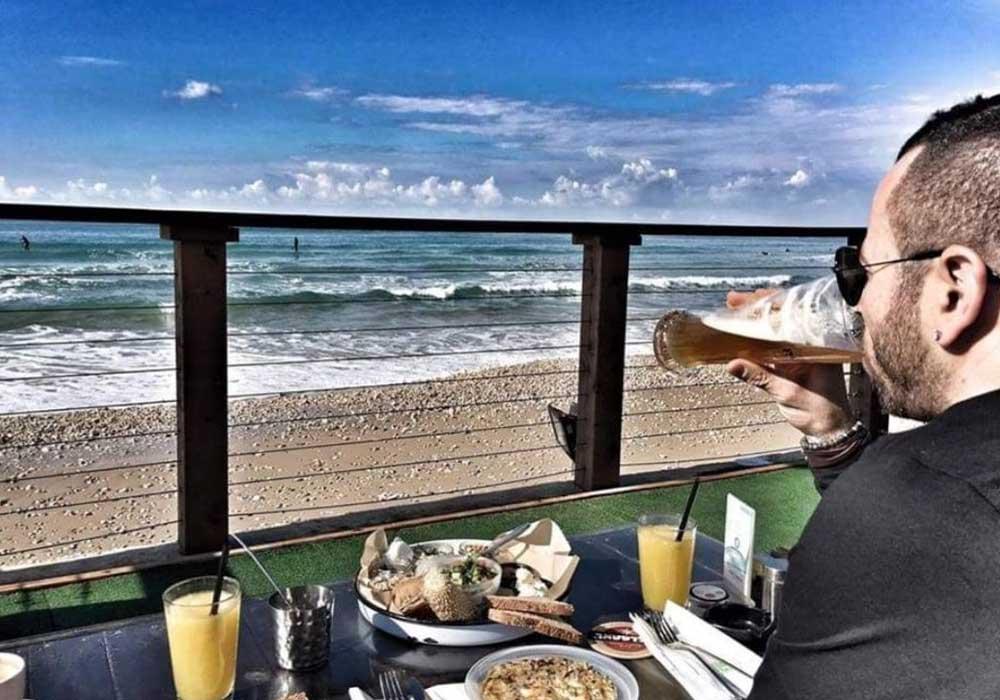לקוח שותה בירה בנירוונה חיפה מול הים